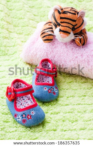 Plush tiger looking at baby shoes. - stock photo