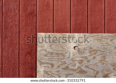 Plywood against red barn - stock photo