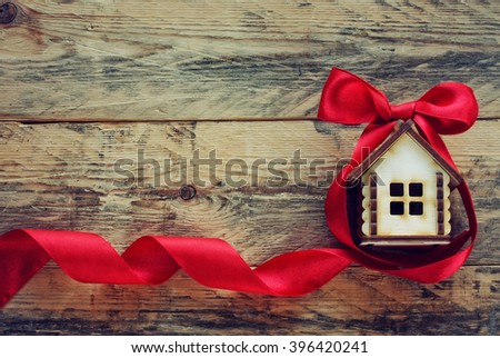 plywood small house with red ribbon on old wooden table - stock photo