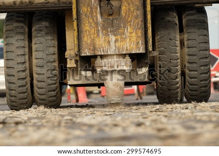 pneumatic hammer drill equipment breaking asphalt at road construction site - stock photo