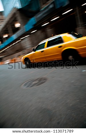 Pnned motion blur of a city street scene with a yellow taxi cab speeding by. - stock photo