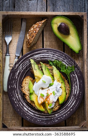 Poached egg and sliced avocado on toasted whole wheat bread on plate. Garnished with scallions and parsley. Table top view - stock photo