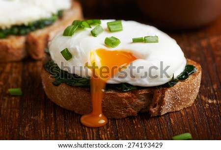 Poached egg on a piece of bread with spinach on the wooden table - stock photo