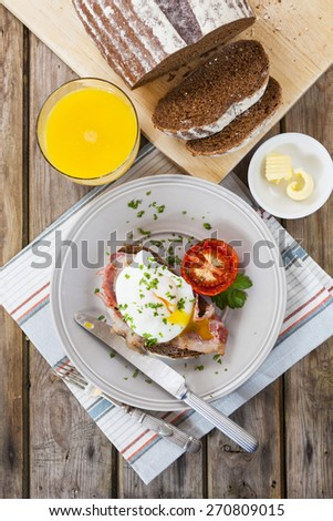 Poached egg on grilled bacon over the slice of rye bread with grilled tomato served with orange juice.