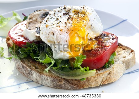 Poached egg on sourdough toast, with grilled tomatoes, mushrooms and salad leaves.  A healthy, delicious breakfast or brunch. - stock photo