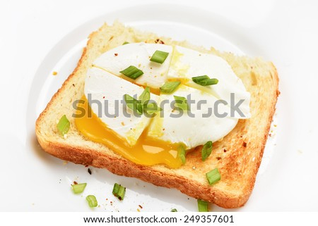 Poached egg on toast over white plate, close up view - stock photo