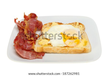 Poached egg on toast with runny yolk and crispy bacon on a plate isolated against white - stock photo