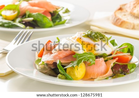 Poached egg salad with smoked salmon, cherry tomatoes and pesto. - stock photo