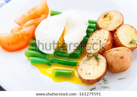 Poached egg with french beans and baked potato - stock photo