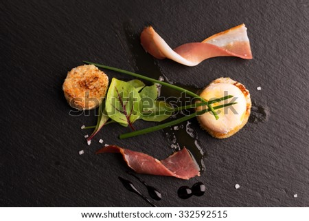 Poached egg with fresh salad and bacon on the black plate - stock photo