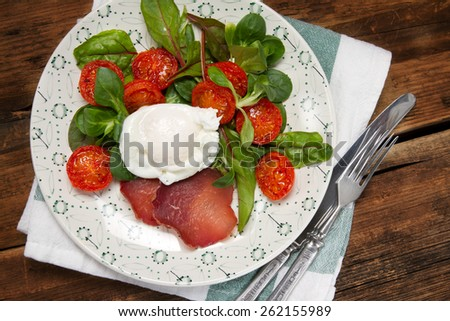 Poached egg with salad, bresaola and stewed cherry tomatoes - stock photo