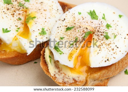 Poached eggs on toasted baguette slices. - stock photo