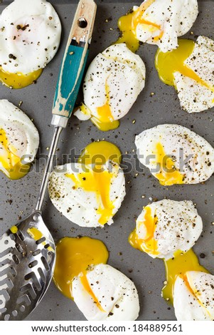 Poached eggs with cracked black pepper, split open - stock photo