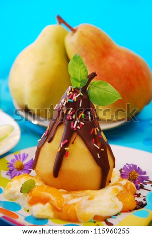 poached pear with chocolate and colorful sprinkles on vanilla sauce as dessert for child - stock photo