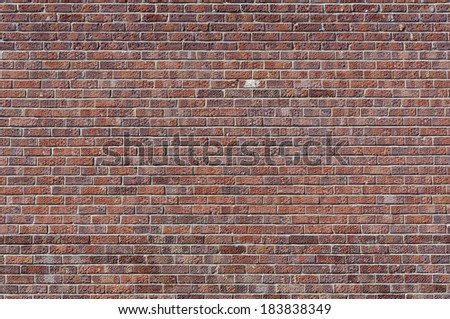 Pocked and stained red brick wall; landscape orientation.