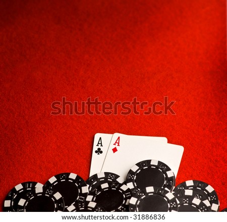 Pocket aces on red felt with black chips and room for copy space - stock photo