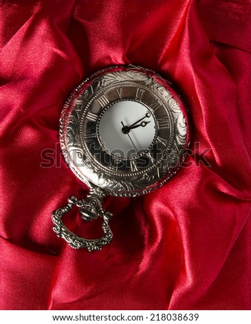 Pocket gray clock on red silk texture - stock photo