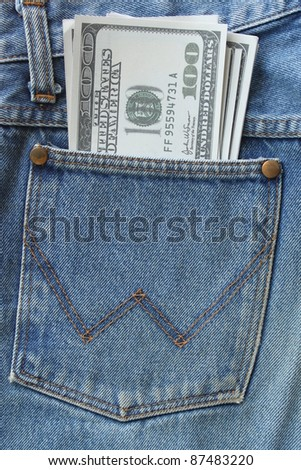 Pocket money. New dollar  in hip pocket of worn blue jeans close-up. - stock photo