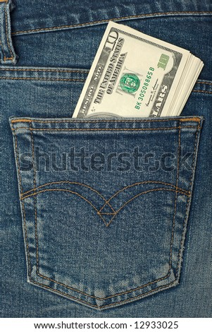 Pocket money. New dollar roll in hip pocket of worn blue jeans close-up. - stock photo