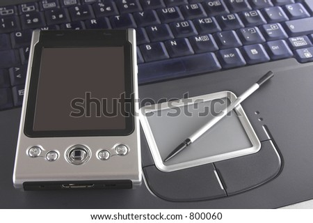 Pocket PC and notebook computer - stock photo