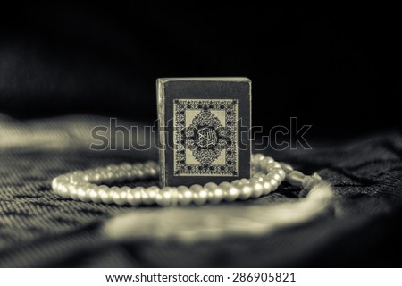 Pocket Quran size with white rosary on a praying rag  - stock photo