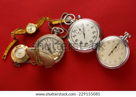 Pocket vintage watch and stopwatch on red - stock photo