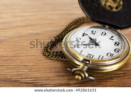 Pocket watch against a rustic wooden background