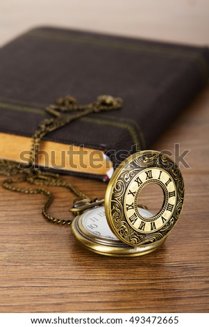 Pocket watch and book against a rustic wooden background