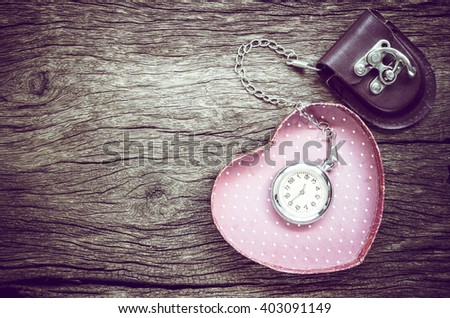 Pocket watch and gift in heart shape on the background. Vintage style. - stock photo