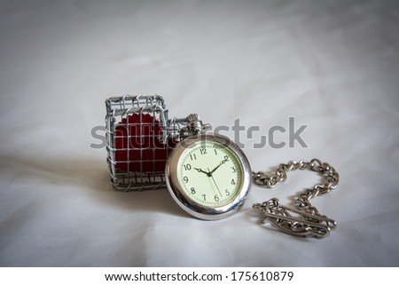 pocket watch and heart in a cage on a tablecloth.
