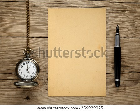 Pocket watch, fountain pen and old paper on wooden table - stock photo