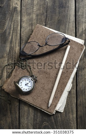 Pocket watch, glasses and old notebook on table, close up - stock photo