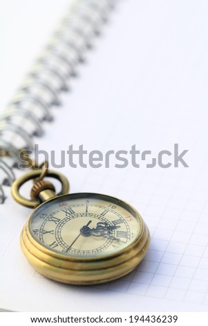 Pocket watch laying on a white notebook page - stock photo
