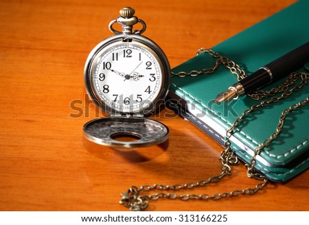Pocket watch near green leather notebook and fountain pen - stock photo