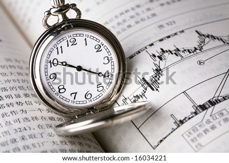 Pocket watch on book about finance