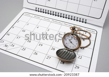 Pocket Watch on Calendar with Grey Background - stock photo