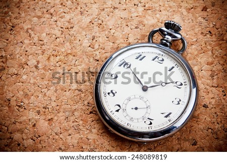 Pocket watch on corkboard background. - stock photo