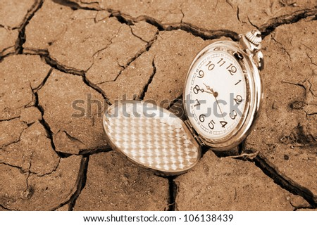 Pocket watch on cracked dry soil - stock photo
