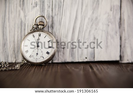 Pocket watch on old wooden background - stock photo