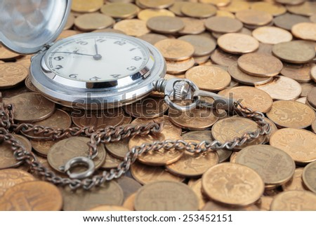 Pocket watch on the coins background - stock photo