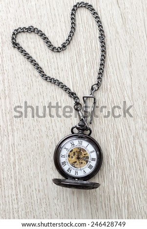 pocket watch on  wooden table, from above - stock photo
