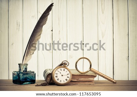 Pocket watch, quill pen, inkwell, book, magnifying glass on the table in front of wooden background - stock photo