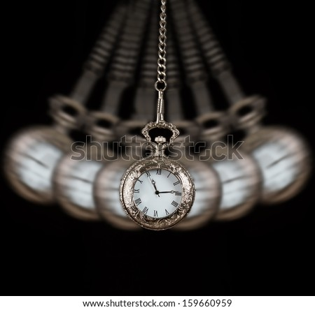 Pocket watch silver swinging on a chain black background to hypnotise - stock photo
