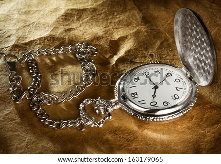 pocket watch with a chain on old paper background - stock photo