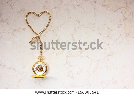 Pocket watch with heart shape chain on marble. - stock photo