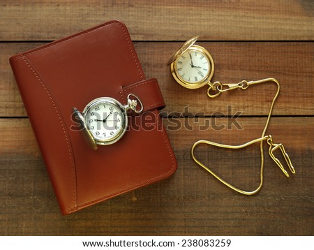 Pocket watches and leather agenda on wooden surface - stock photo