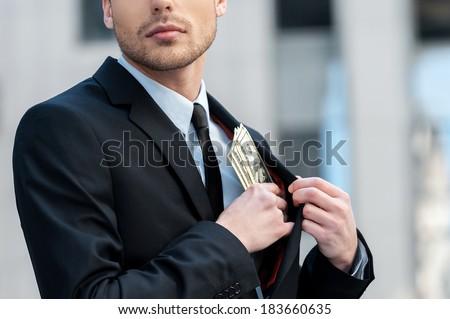 Pocketing company money. Cropped shot of a businessman placing money into his pocket - stock photo