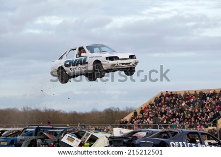 PODINGTON, UK - FEBRUARY 22: An unnamed stunt driver attempts to jump his modified car over seven parked cars at the Santa Pod Raceway Stuntfest event on February 22, 2014 in Podington - stock photo