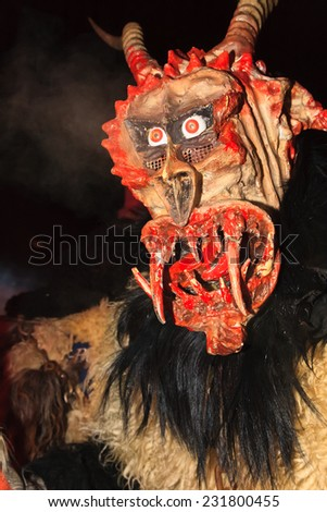 "PODKOREN, SLOVENIJA - NOVEMBER 29th: Unidentified man wears Krampus (devil) mask at traditional procession on November 29th 2013 ""Parkelj gathering"" in Podkoren, Slovenia"