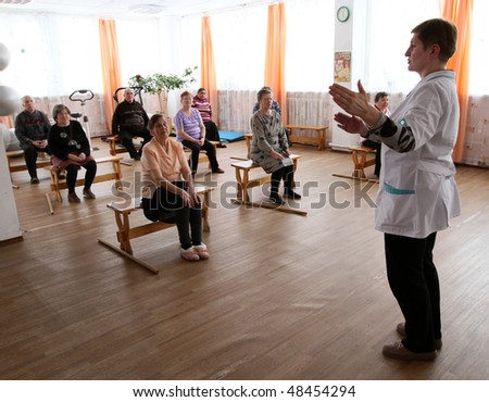 PODPOROZHYE, RUSSIA - MARCH 11: Day of Health in Center of social services for pensioners and the disabled Otrada (gymnastics with sticks for eldery), March 11, 2010 in Podporozhye, Russia. - stock photo